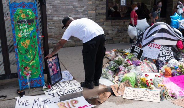 A man leaves a photograph at a memorial for George Floyd on Wednesday afternoon, after the death of Floyd on Monday night in Minneapolis, Minnesota