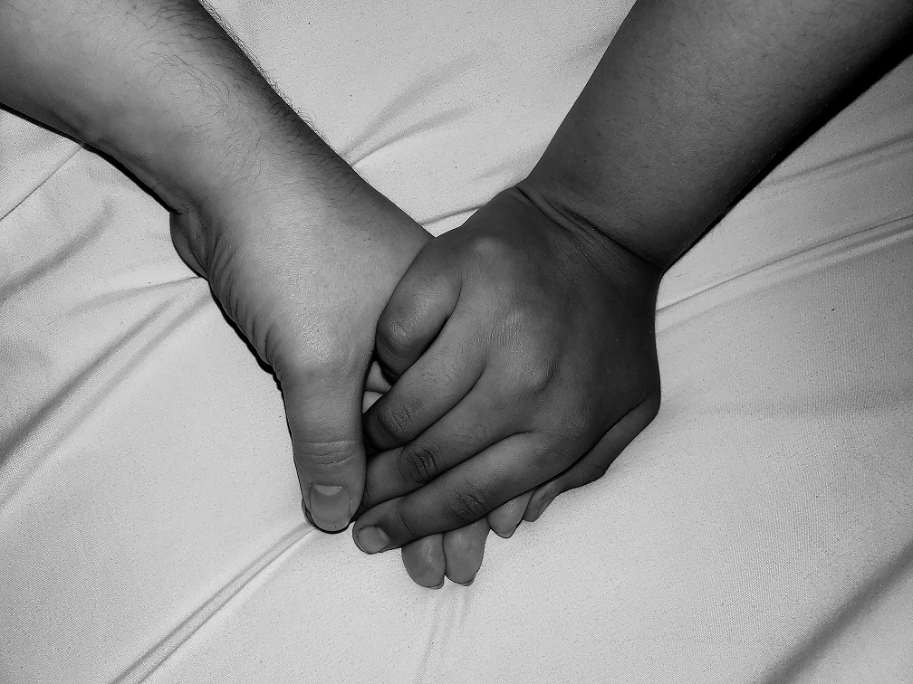 Black and white photograph of holding hands, one light skinned, one dark skinned.